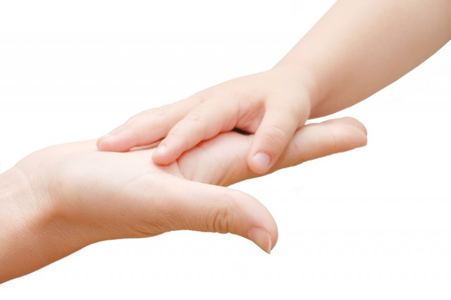 Small kids hand in woman hand on white