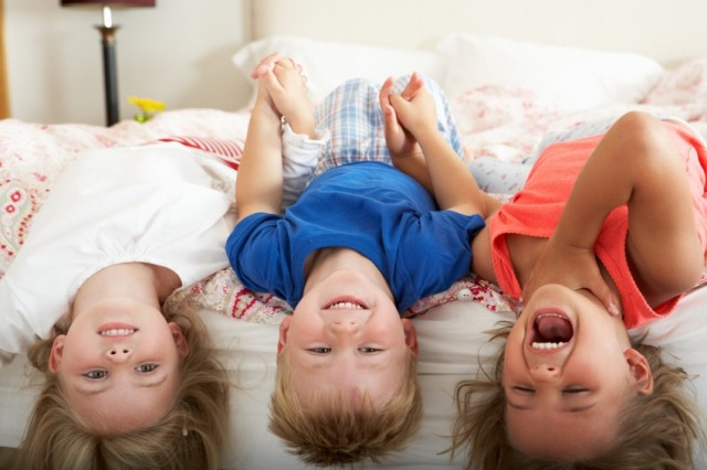 Children Lying Upside Down Bed