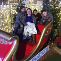 Chelsea and her family posing in a sleigh at Christmas