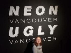 Girl posing in from of Neon Vancouver sign at Museum of Vancouver
