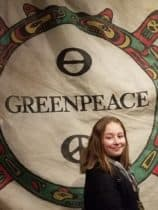 Girl standing in front of Greenpeace sign