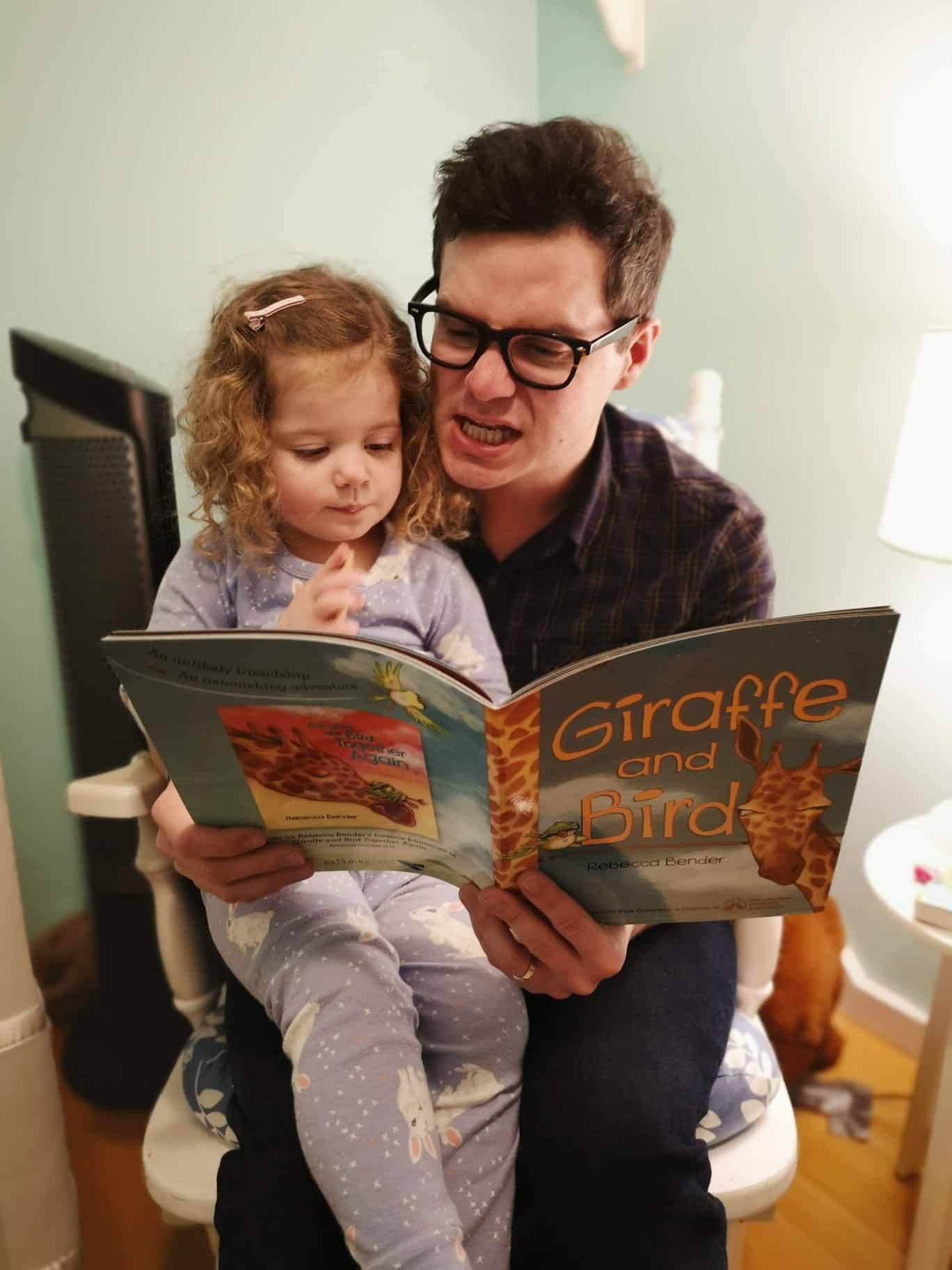 James R.C Smith reading a book with his daughter