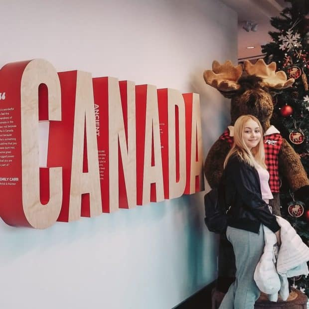 girl posing in front of large canada sign