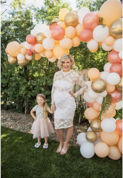 Mom and daughter posing beside balloons