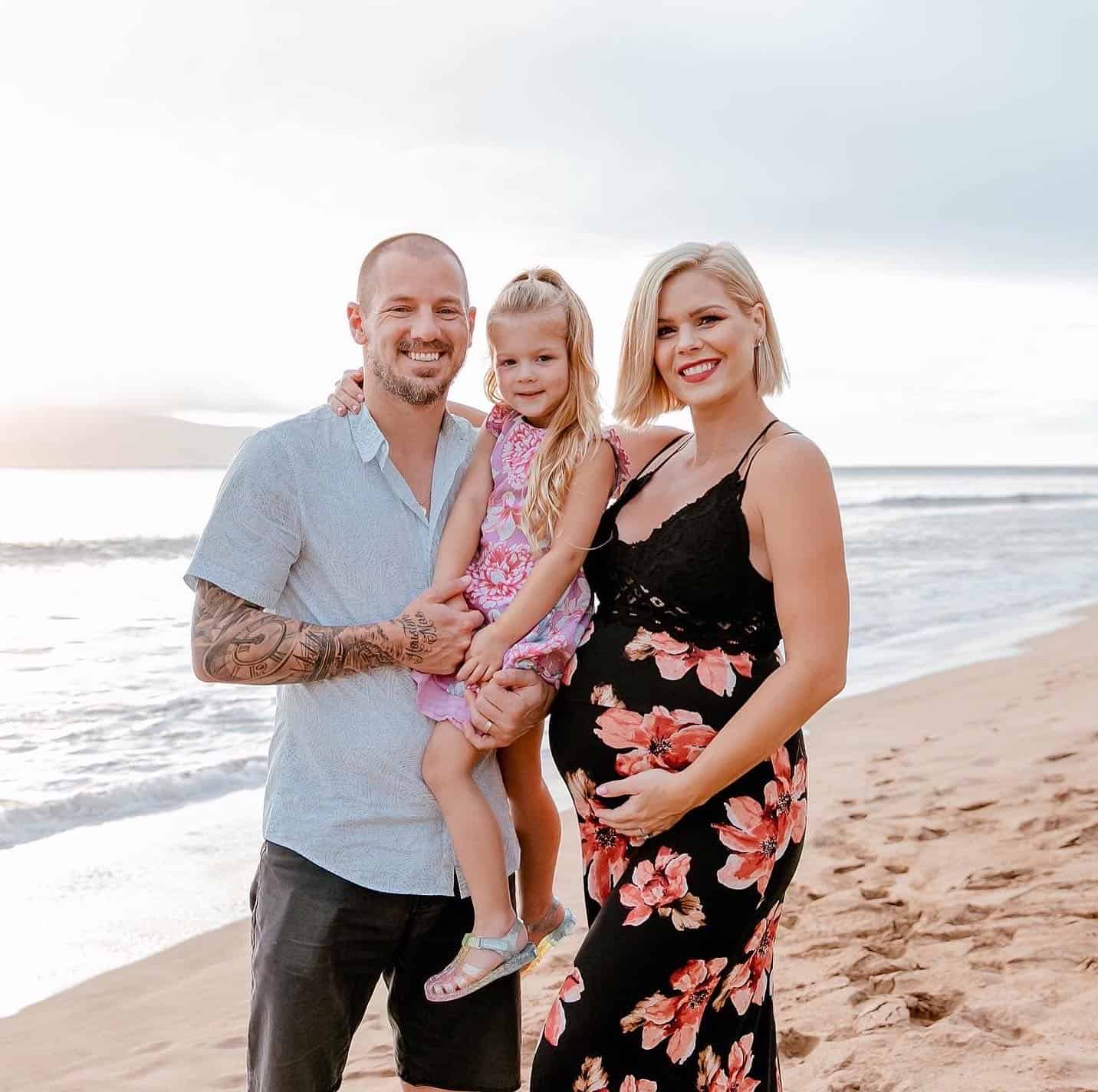 Kim standing on beach with husband and daughter