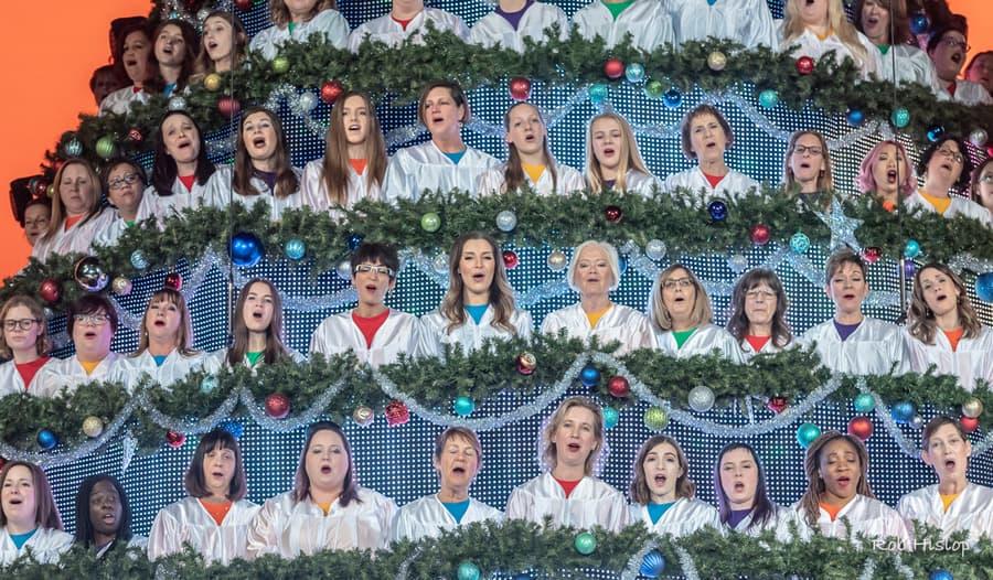 People in a Christmas tree display singing