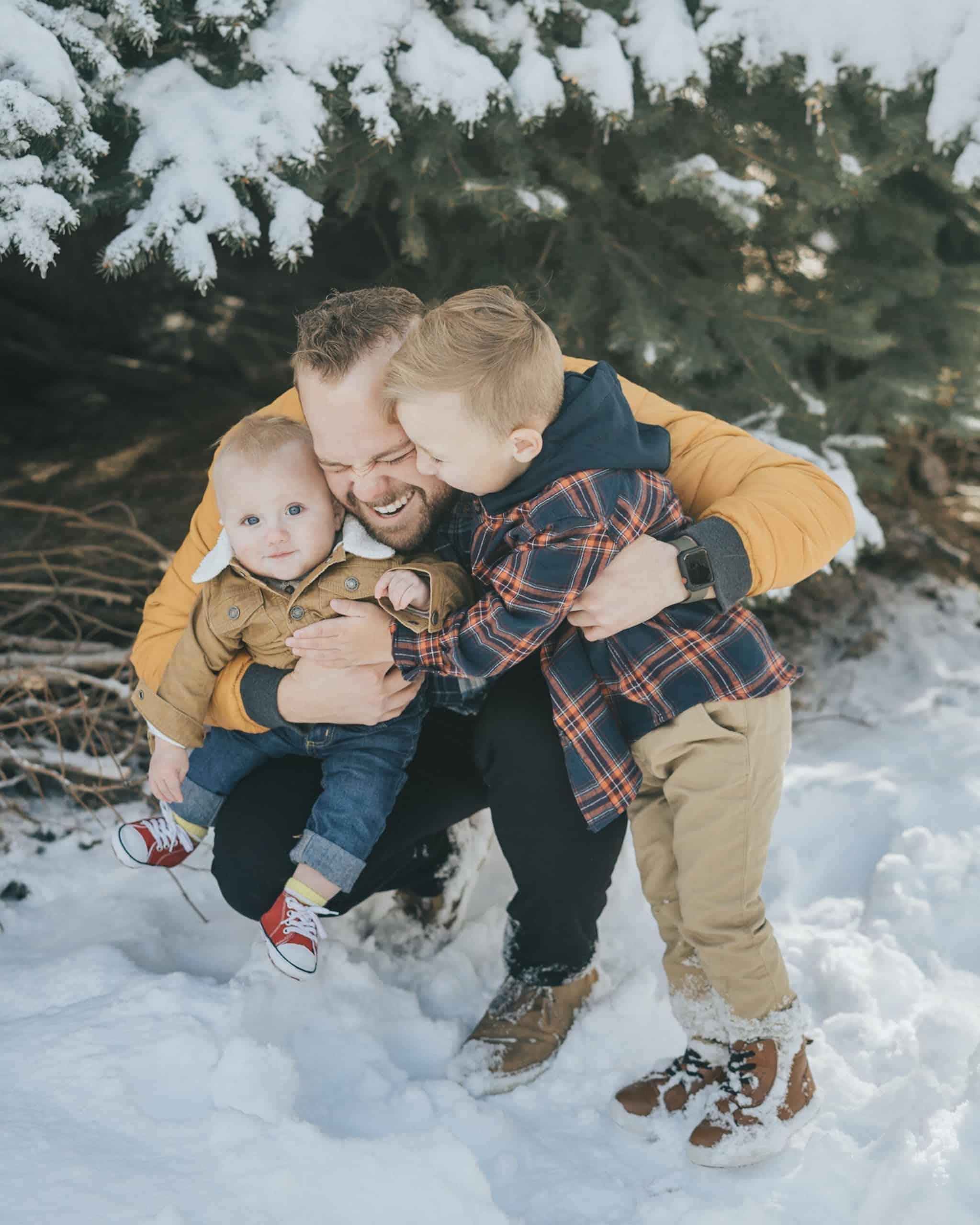 Andrew hugging his children in the snow