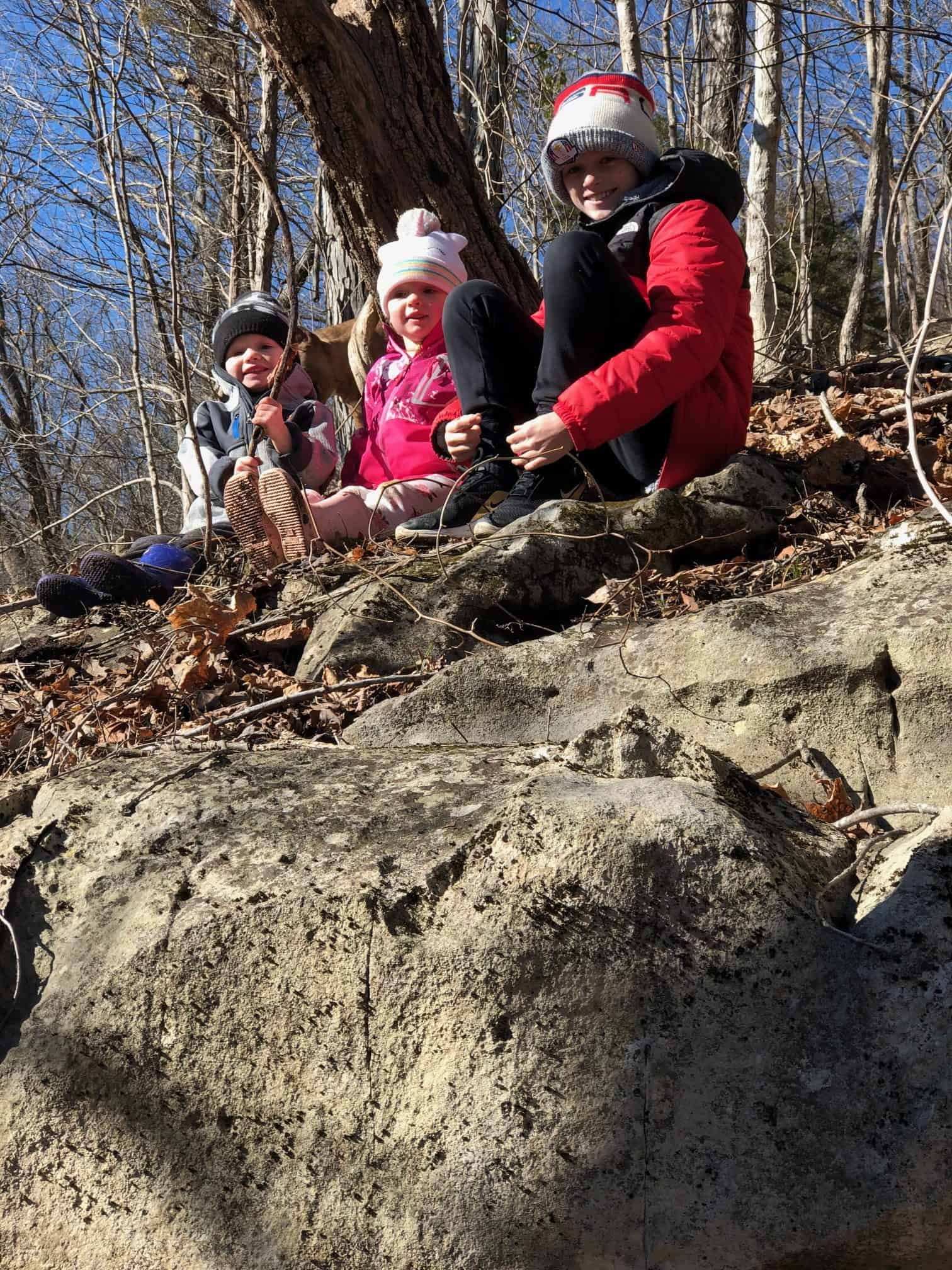 Taylor McKinney's children outdoors on a rock