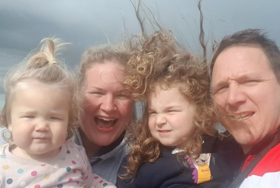 Joe taking a selfie with his family on a windy day