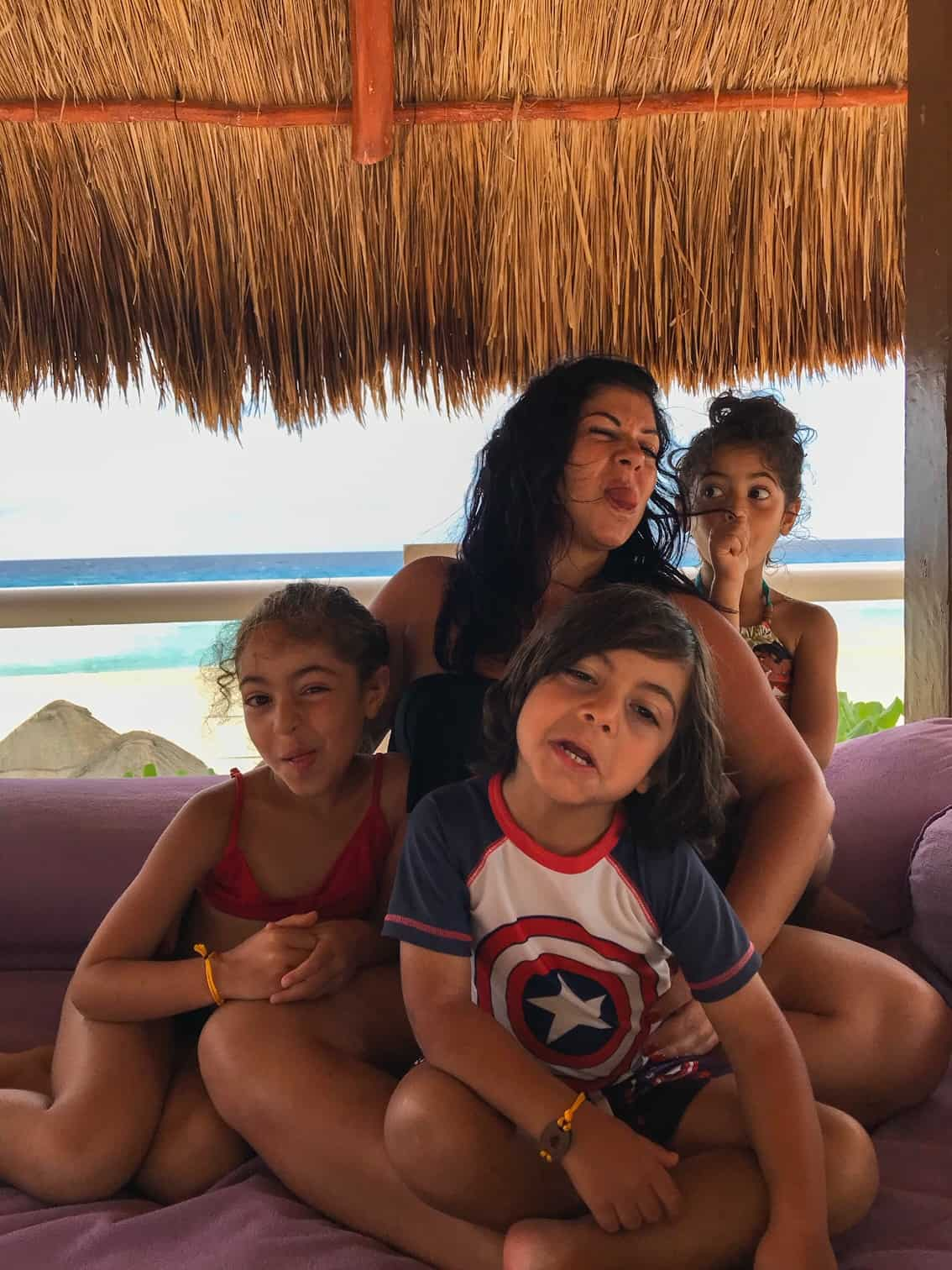 Pina making funny faces with her children at the beach